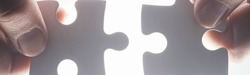 Cropped shot of hands holding two puzzle pieces